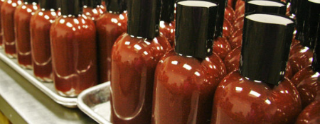 A row of unlabeled cylindrical bottles of hot sauce on a silver tray, with black caps.